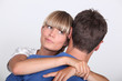 Young woman hugging her boyfriend with a look of uncertainty