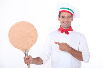 Italian chef pointing at a wooden pizza peel