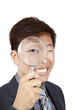 asian businessman holding magnifier over his eye