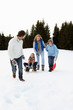 Young Family In Alpine Snow Scene With Sled