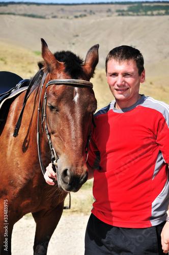smiling man petting his horse