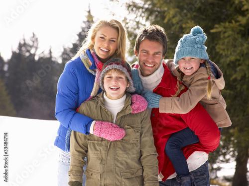 Young Family  In Alpine Snow Scene