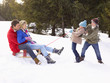 Young Girl And Boy Pulling Parents Through Snow On Sled
