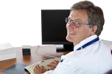 Älterer Arzt sitzt am Schreibtisch und tippt Patientenakte