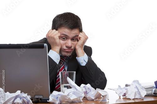 Verzweifelter Mann sitzt über Papierflut am Schreibtisch