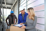 Manager with storemen controlling goods delivery