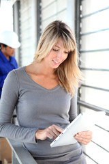 Businesswoman in warehouse using electronic tablet