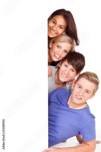 vier junge leute mit hinweisschild