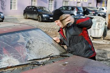 Hooligan smashing windshield