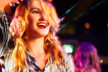 Woman in club or bar having fun (motion blur!)