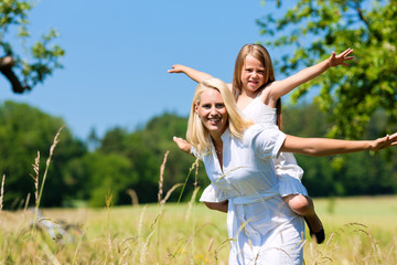 Mother with daugther in summer on meadow