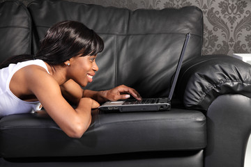 Beautiful black woman at home using facebook