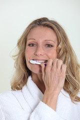 Woman in bathrobe cleaning teeth