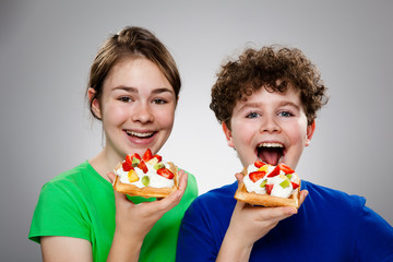 Kids eating cake with cream and fruits