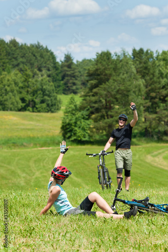 Sport mountain biking couple greeting in meadows