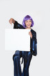 Woman in Seventies costume and wig holding blank board