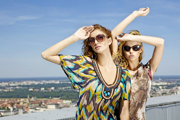 two beautiful girl in sunglasses on background blue sky