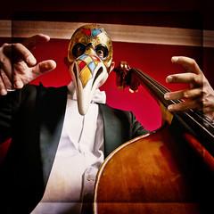 Musicista con la maschera del medico della peste e contrabbasso