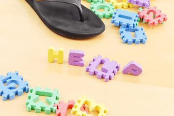 Letters Spelling the Word Help on Floor with Mommys Slipper