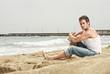 Handsome man sitting on a beach