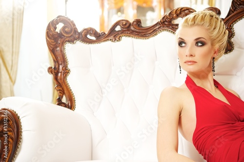 Blond woman sitting on luxury sofa