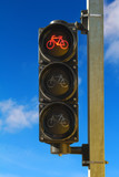 Sunlit red bicycle traffic lights on a sky background