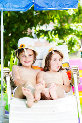 Two little girls sitting on chair and enjoing in summer
