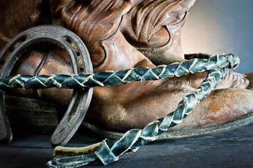 Cowboy  boots,horseshoe and whip on wood