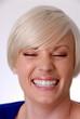 Frau lacht und zeigt viele Zähne