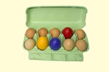trois oeufs de couleur dans une boite de douze