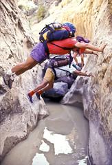 Hikers navigate a slot canyon.