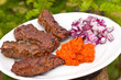Traditional cevapcici with ajvar paste and red onion