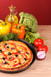 tasty pizza with olives and vegetables on red background