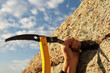 Hands rock-climber hammering in hook in rock