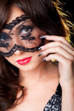 Attractive brunette with lacy mask on eyes poster