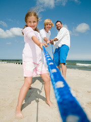 Tug-of-war - family team playing on the beach