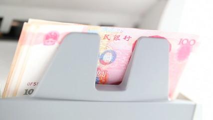 Electronic money counter processing yuan 100 bills.