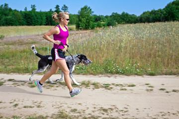 Walking a dog in summer nature, woman runner
