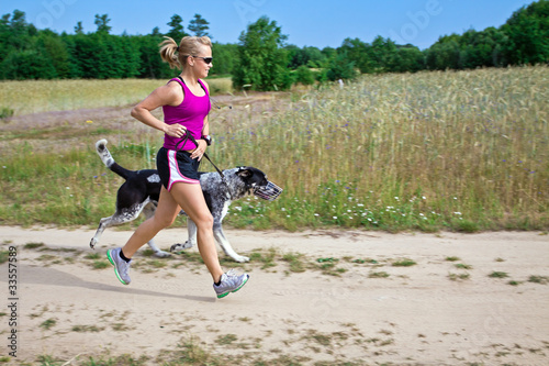 Walking a dog in summer nature, woman runner