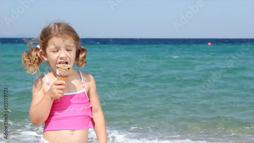 little girl eat ice cream on beach