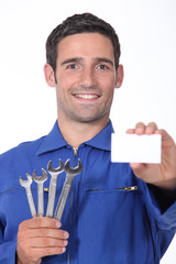 a 35 years old mechanician is showing a business card
