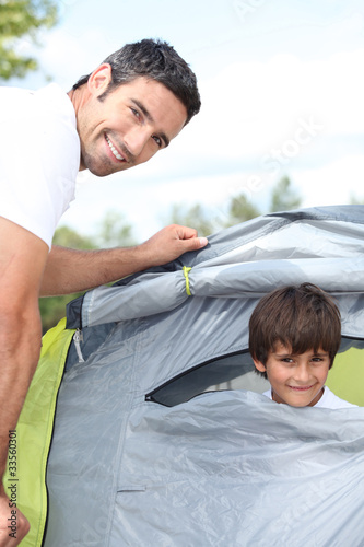 a 35 years old man and a little boy inside a canvas tent