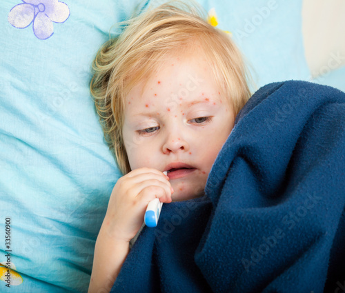 a sick girl is measuring the temperature