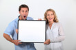 Couple looking surprised with white board