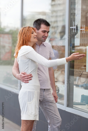 married couple to stand at a shop show-window.