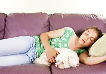 Teenage girl and her dog sleeping together on a sofa