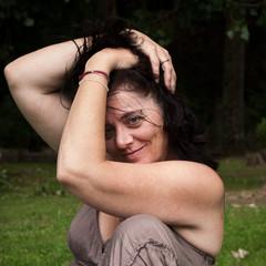 portrait femme brune en robe décoletée se touchant les cheveux