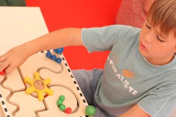 enfant jouant avec un jeu en bois