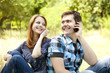 Couple calling by mobile phone at outdoor in summer time.