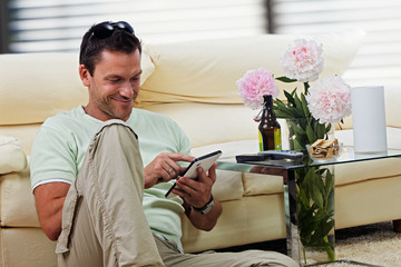 man relaxing in the living room, with tablet-pc